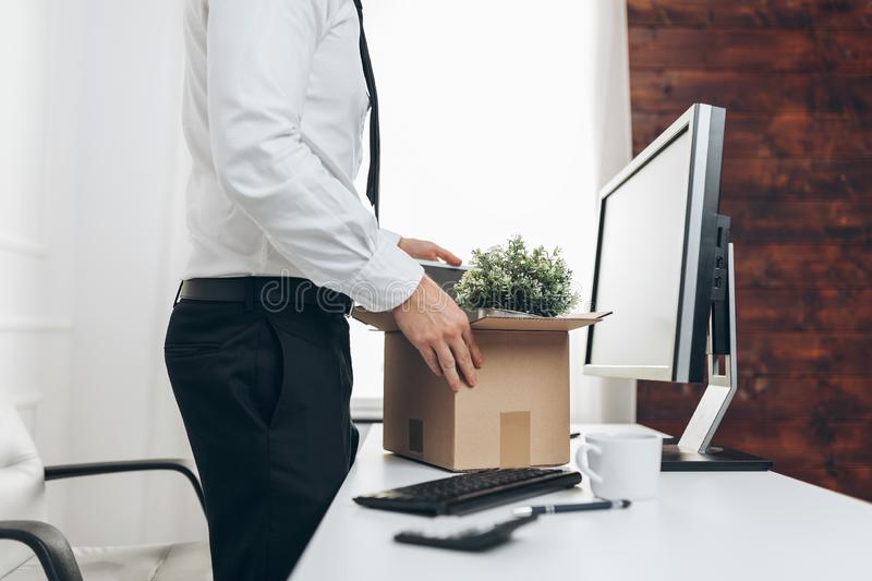 Businessman clearing his desk after being made redundant. Dissapointed businessman clearing his desk after being made redundant stock photo