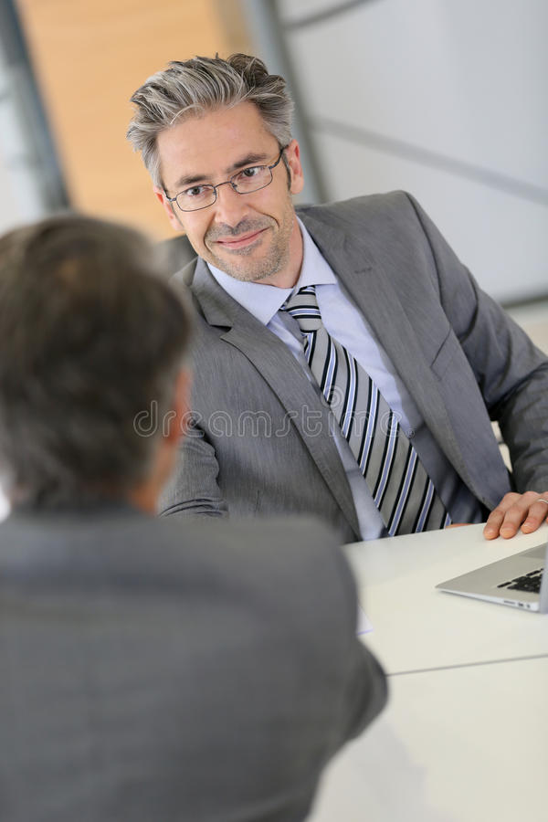 Businessman and client handshaking stock photo