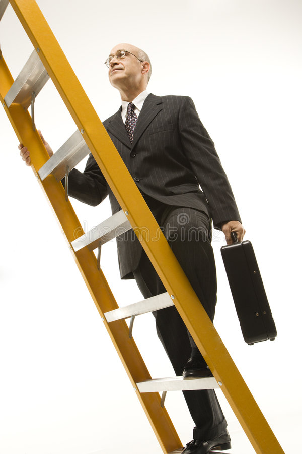 Businessman climbing ladder. stock photos