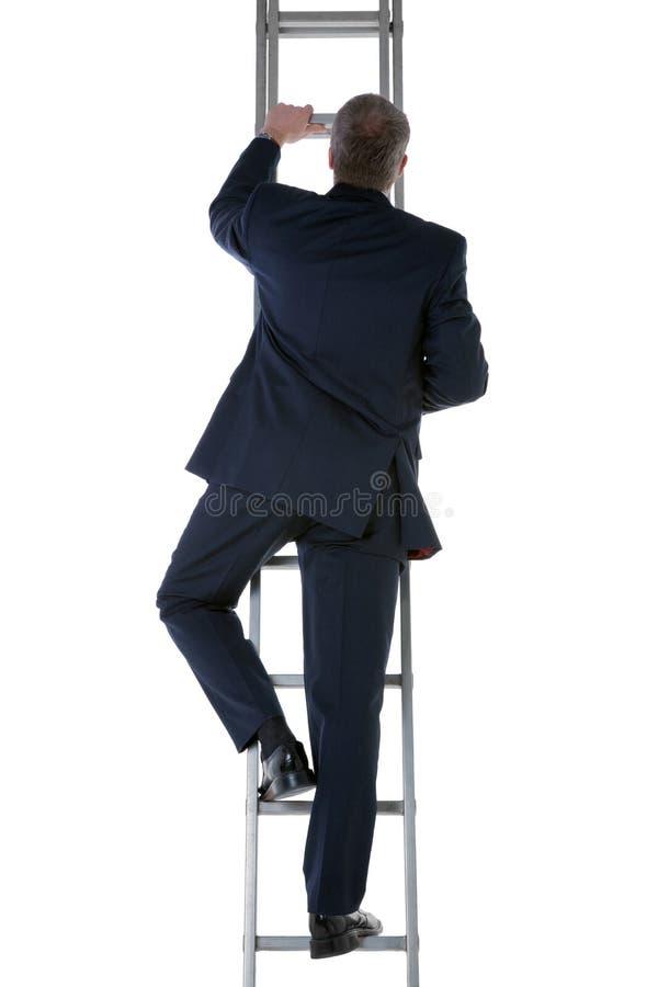 Businessman climbing a ladder royalty free stock photos