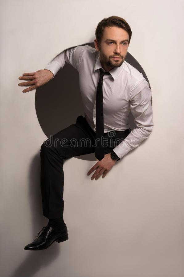 Businessman climbing out of a circular hole royalty free stock photography