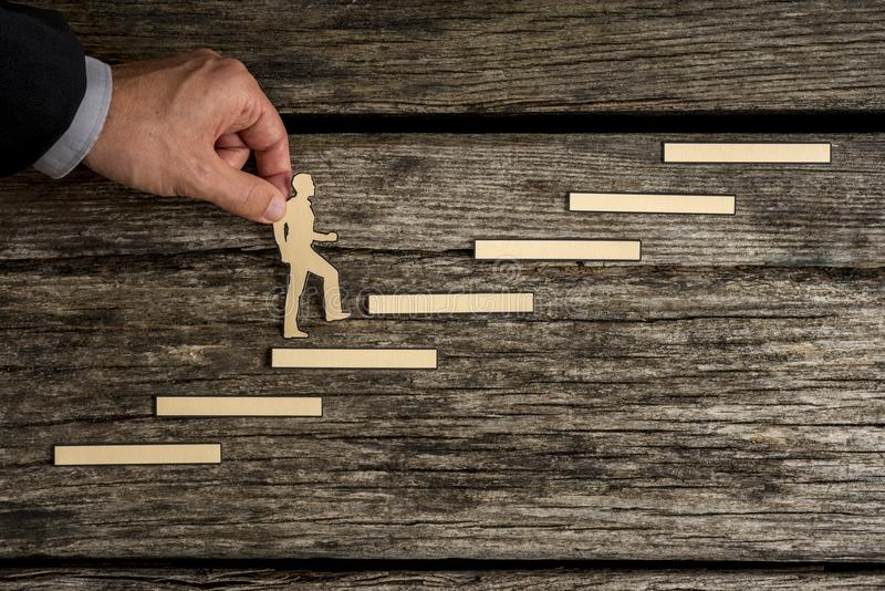Businessman climbing the steps to success. In a conceptual image with paper silhouette cutouts of a man and a human hand helping him climb over rustic wood with royalty free stock photos