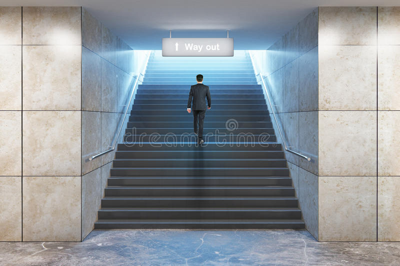 Businessman climbing success stairs. Success concept. Businessman climbing illuminated underground staircase with `way out` sign. 3D Rendering stock image