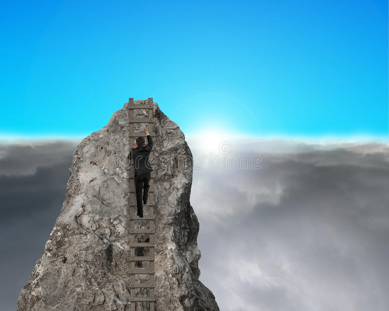 Businessman climbing to top of rocky mountain with sunrise stock image