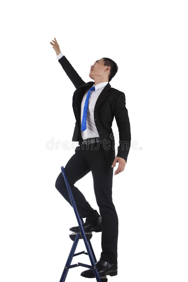 Businessman climbing up a ladder royalty free stock photos