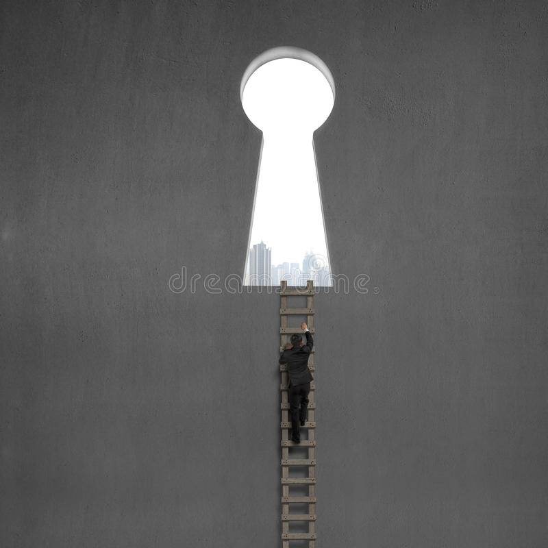 Businessman climbing on wooden ladder to key shape door stock photo
