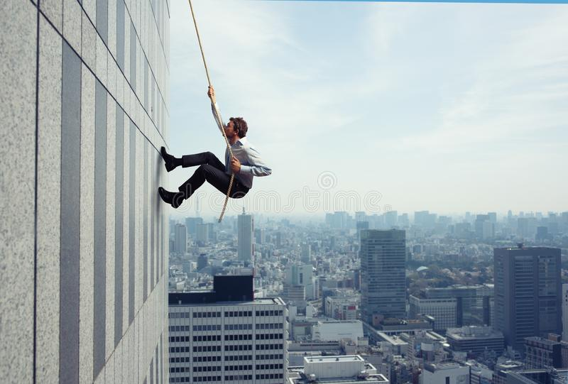 Businessman climbs a building with a rope. Concept of determination royalty free stock images