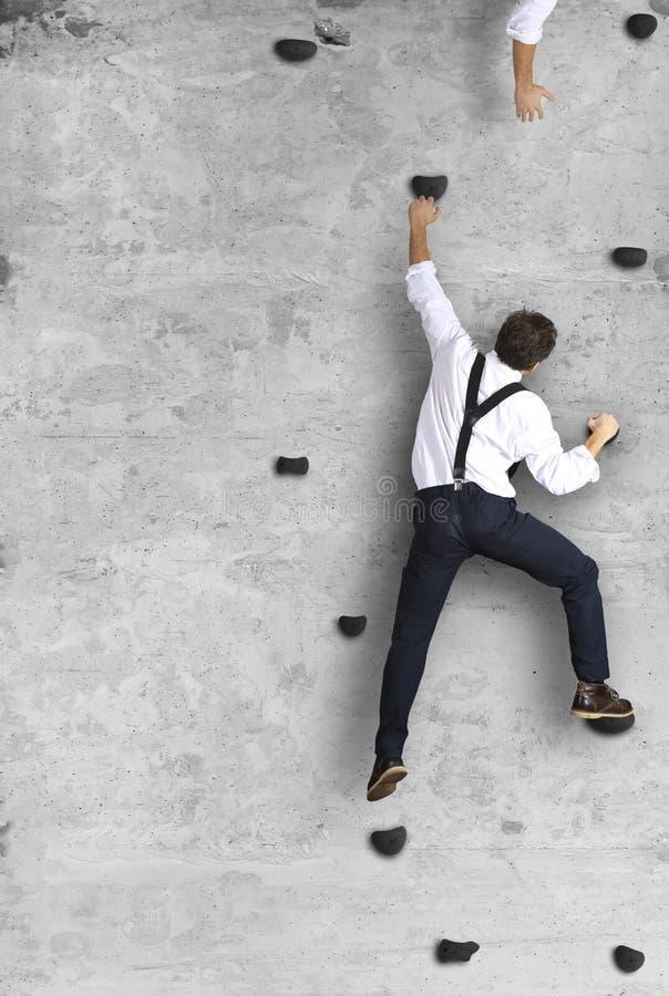 Businessman climbs the wall as a climber stock photo