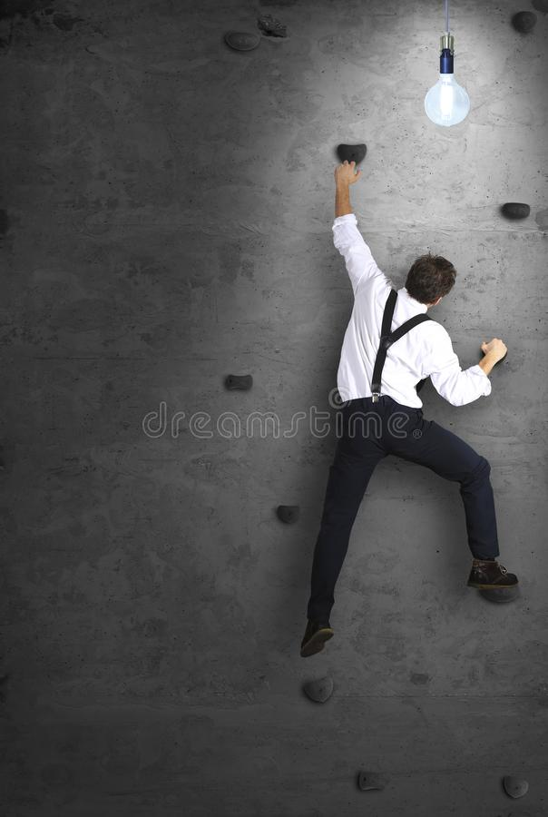 Businessman climbs the wall as a climber royalty free stock photography