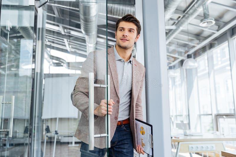Businessman with clipboard entering the door in office. Handsome young businessman with clipboard entering the door in office stock images