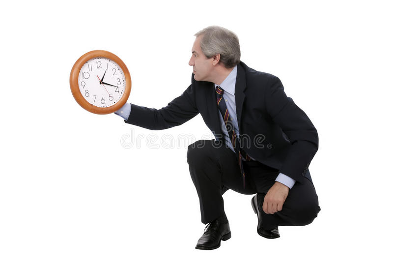 Businessman with clock. Mature businessman looking at time on large clock, isolated on white background royalty free stock photography