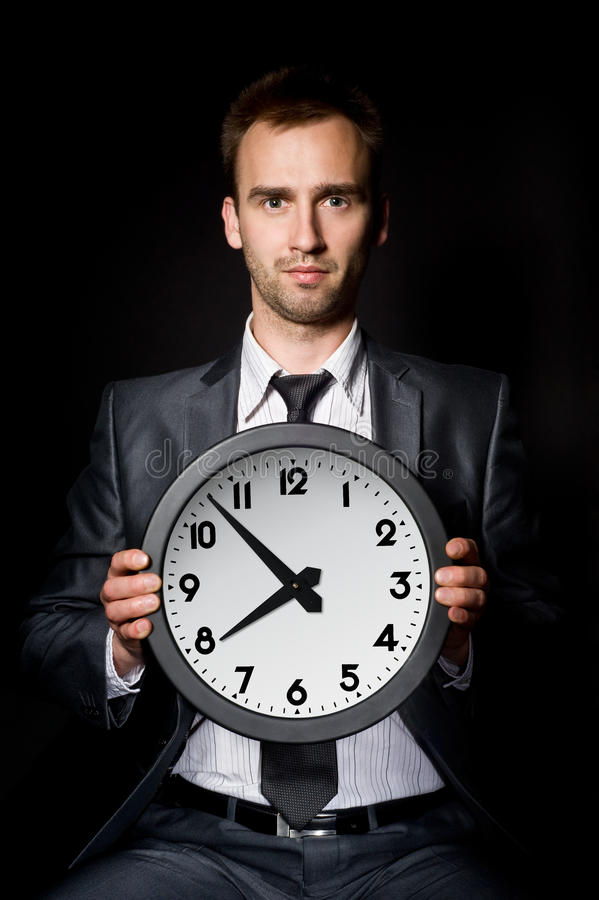 Businessman with clock. Young handsome businessman holding clock, over black royalty free stock images