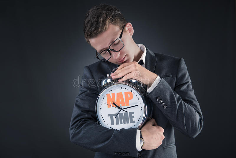 The businessman with clock sleeping in business concept. Businessman with clock sleeping in business concept stock photo