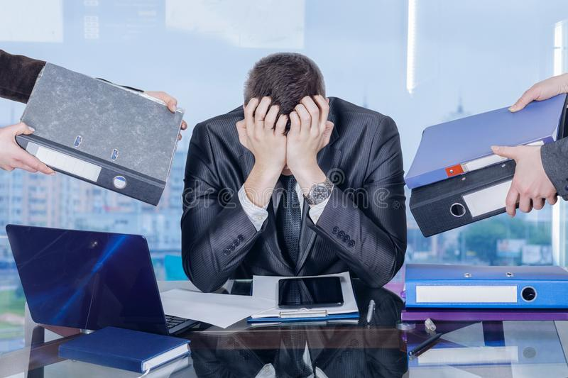 A businessman is closing his face with his hands in working stress assault stock photos