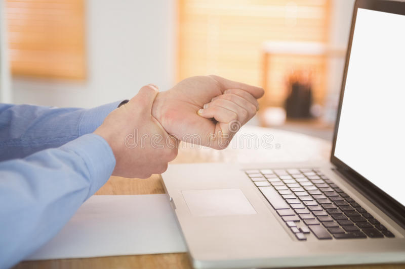 Businessman clutching his painful wrist. In his office stock photography
