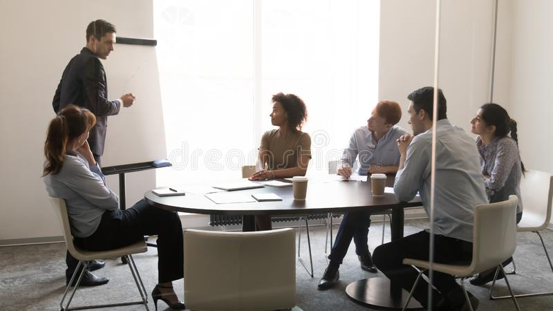 Businessman coach giving presentation on whiteboard at team business training. Businessman coach teacher giving presentation on whiteboard at sales team business royalty free stock image