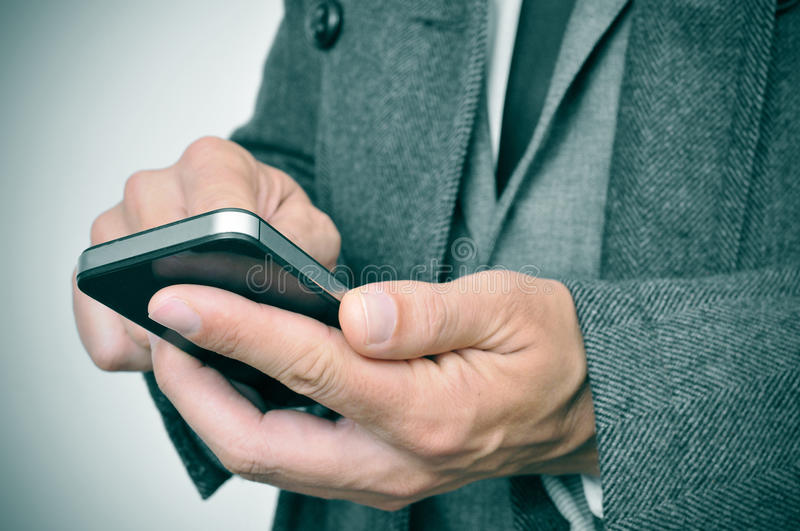Businessman in coat using a smartphone stock photography
