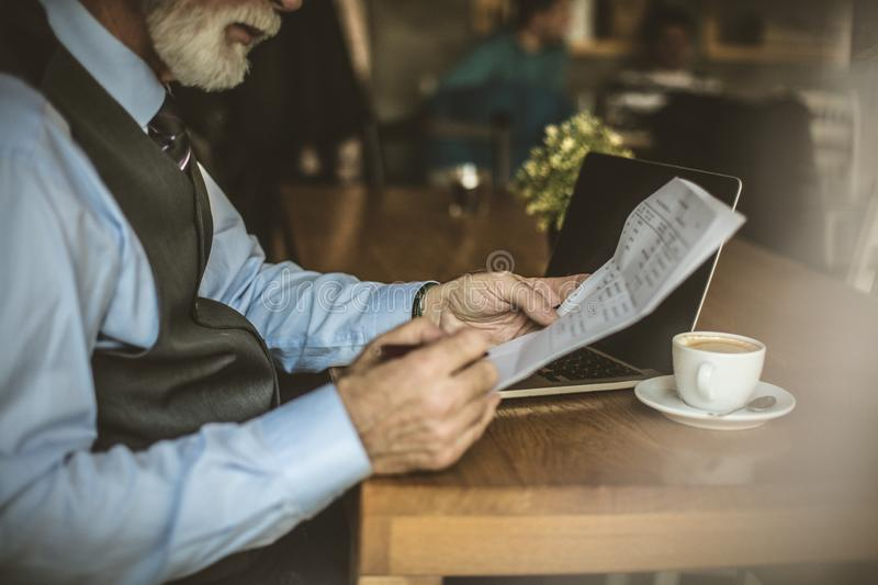 Businessman at coffee shop working on his laptop. Senior businessman at coffee shop working on his laptop royalty free stock photo