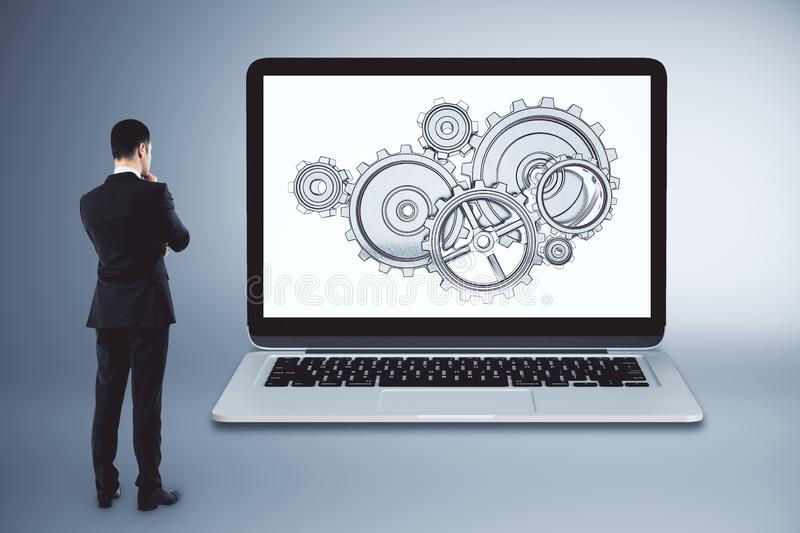 Businessman with cogwheels. On laptop screen. Teamwork and engineering cocnept stock image