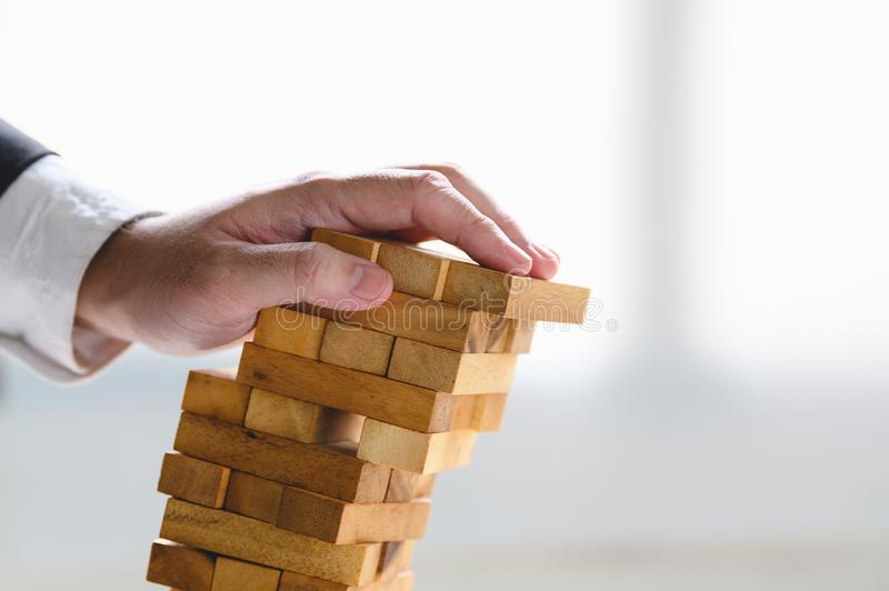 Businessman collapsing stacked tower wood block by hand as failure or bankrupt project. Business organization and company stock photo