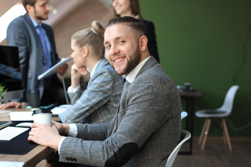 Businessman with colleagues in the background in office. Businessman with colleagues in the background in office stock photography