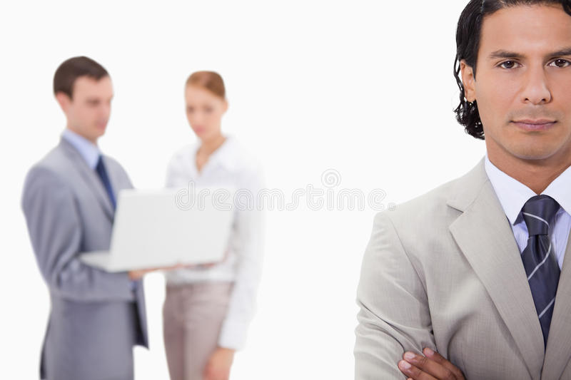 Businessman With Colleagues With Laptop Behind Him Royalty Free Stock Images
