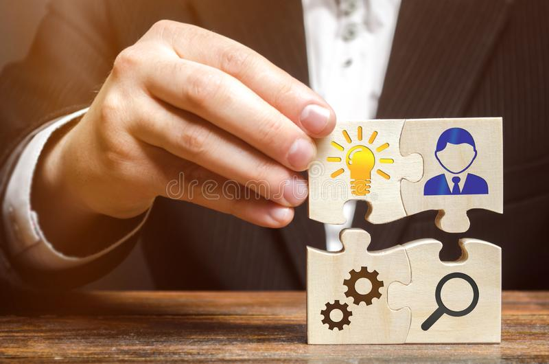 Businessman collects puzzles with the image of the attributes of doing business. Strategy planning concept. Organization of the stock images