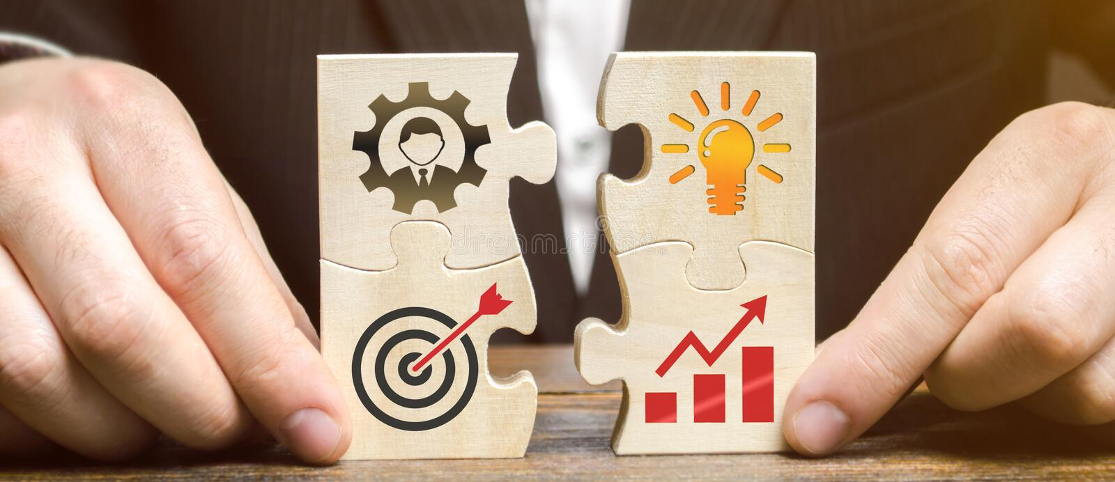 Businessman collects puzzles with the image of the attributes of doing business. Strategy planning concept. Organization of the stock photo