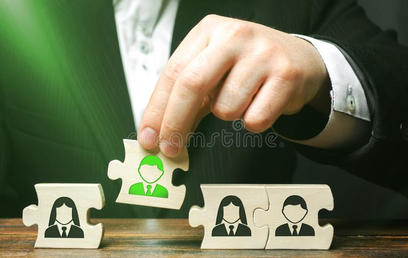 A businessman collects puzzles symbolizing a team of employees. The concept of creating a business team to perform tasks. Toxic. Employee, weak link. Management stock photo