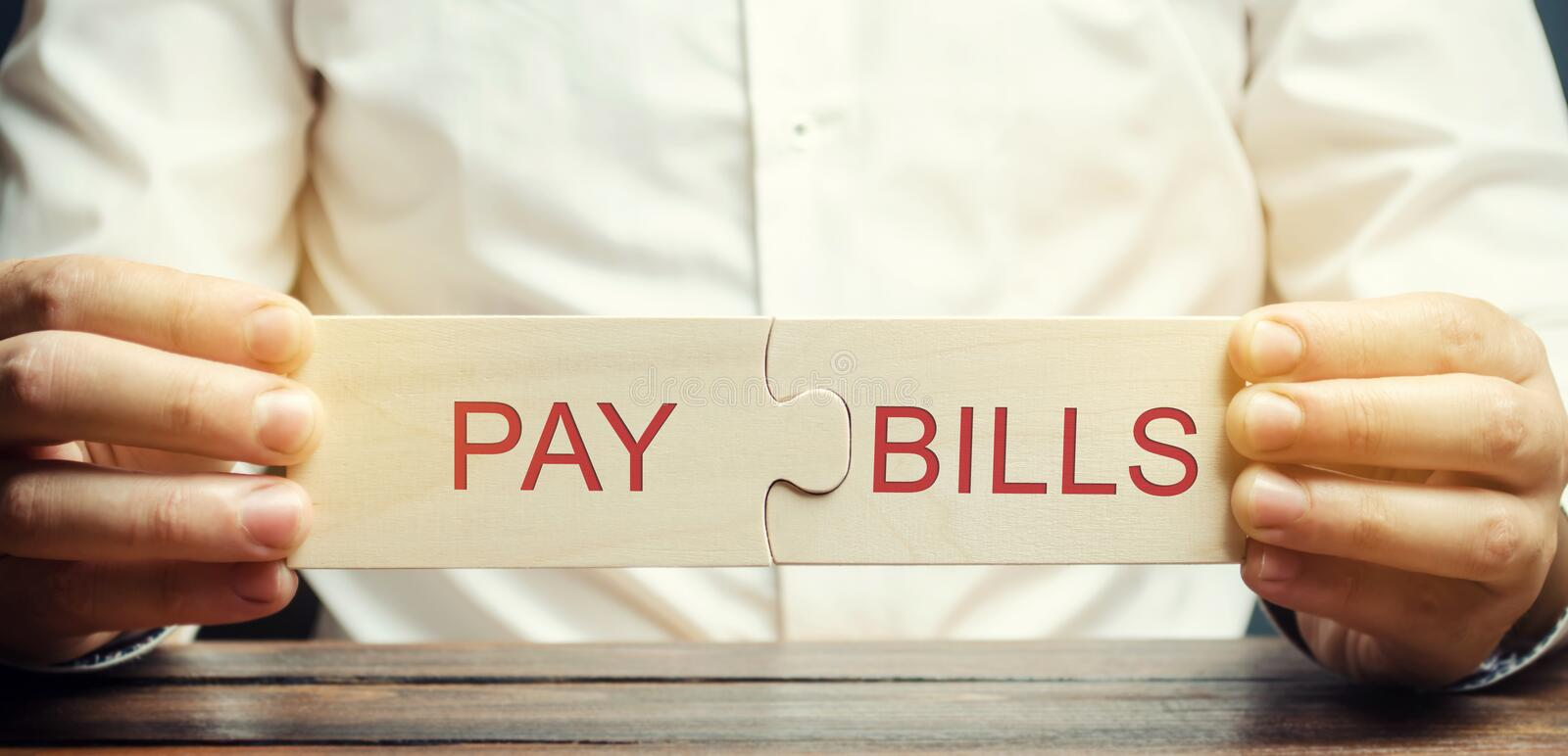 Businessman collects puzzles with the word Pay bills. Online payment a bill for utilities. Direct debit. The medicine. Mortgage royalty free stock image