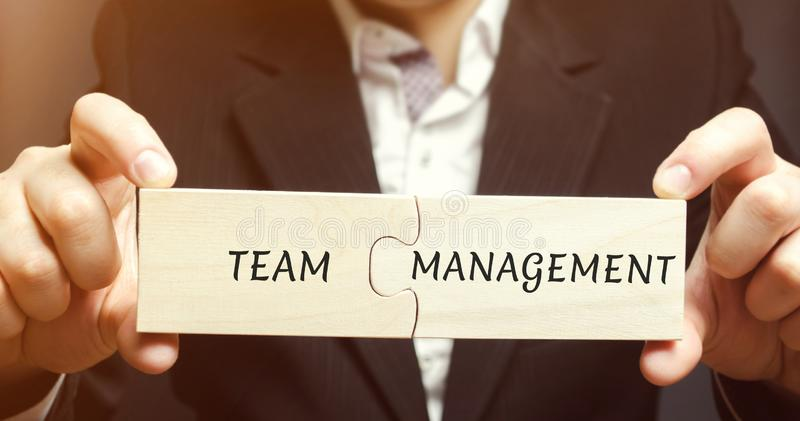 Businessman collects puzzles with the words Team management. Increase efficiency. Hiring and dismissal employees. Organization of stock photography