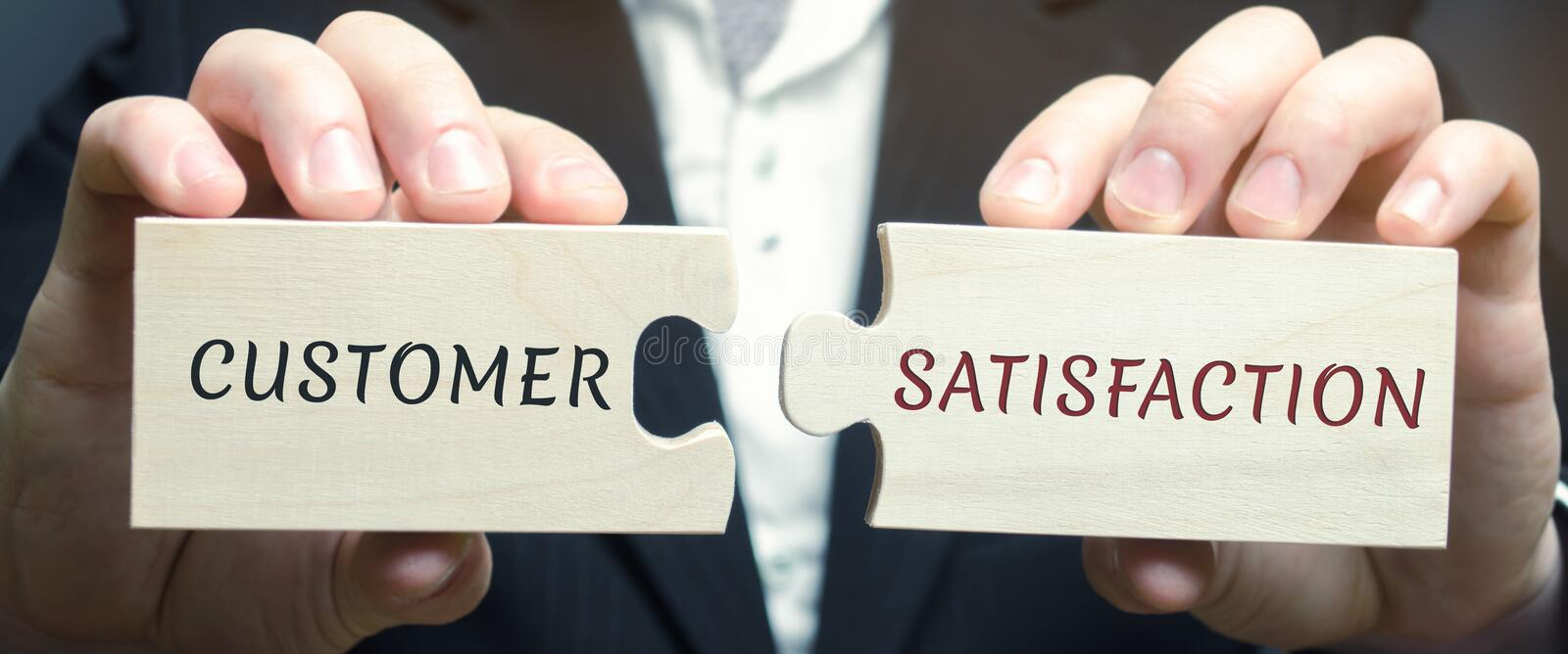 Businessman collects wooden puzzles with the word Customer Satisfaction  CSat . It is a measure of how products and services royalty free stock photography