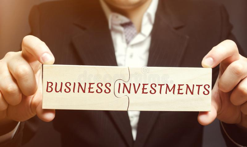 Businessman collects wooden puzzles with the words business investments. Increase capital. Investing your assets in your own or royalty free stock image