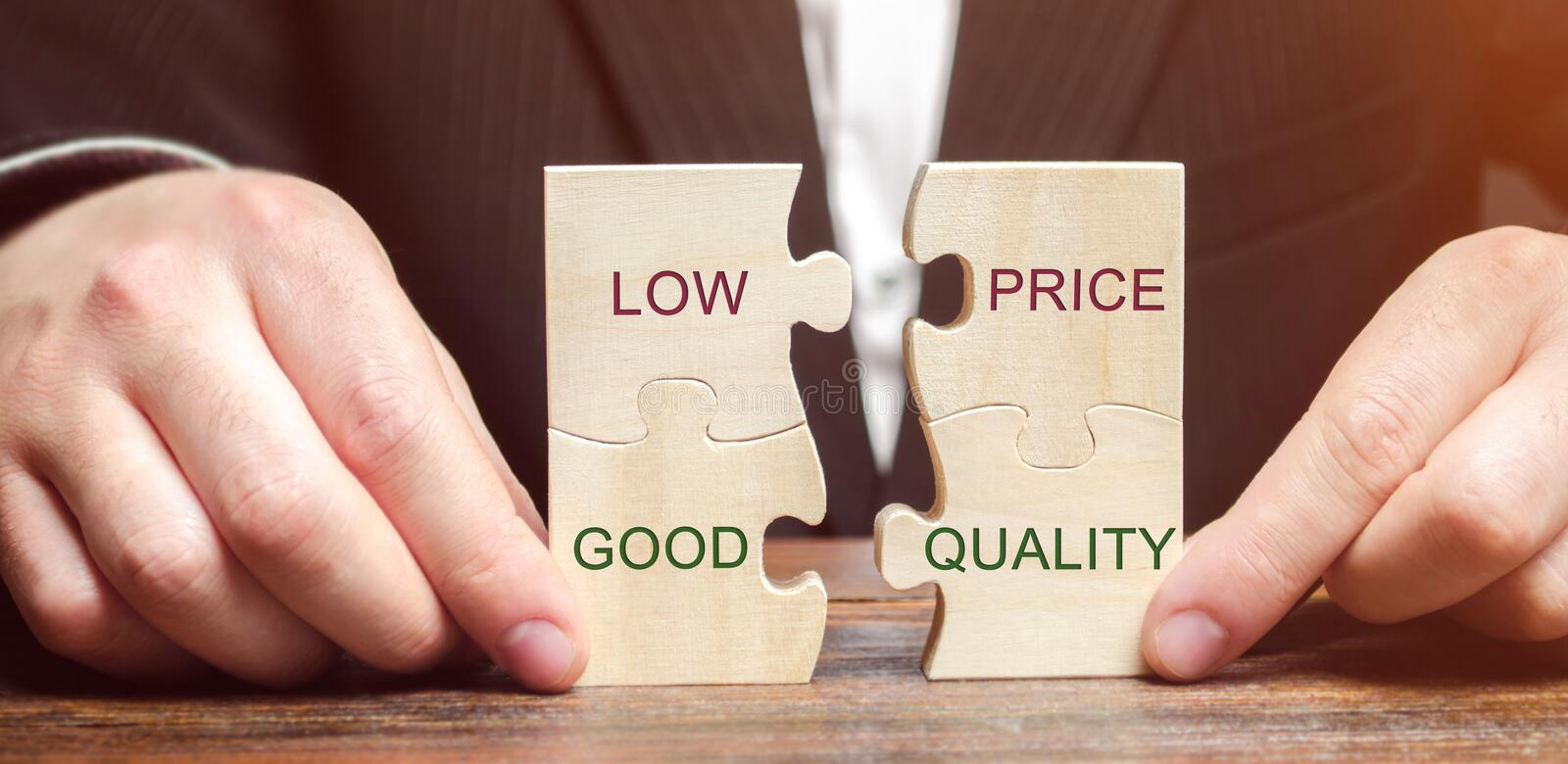 A businessman collects wooden puzzles with the words Low price - good quality. The concept of profitable deals for buyers. Small royalty free stock image