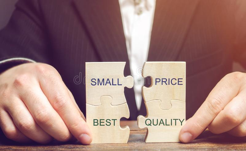A businessman collects wooden puzzles with the words Small price - best quality. The concept of profitable deals for buyers. Low stock image