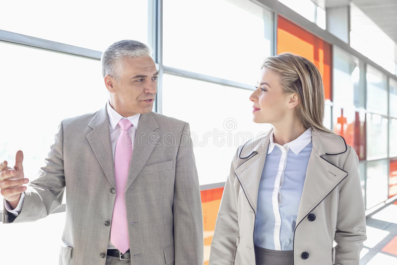 Businessman communicating with female colleague while walking in railroad station stock photos