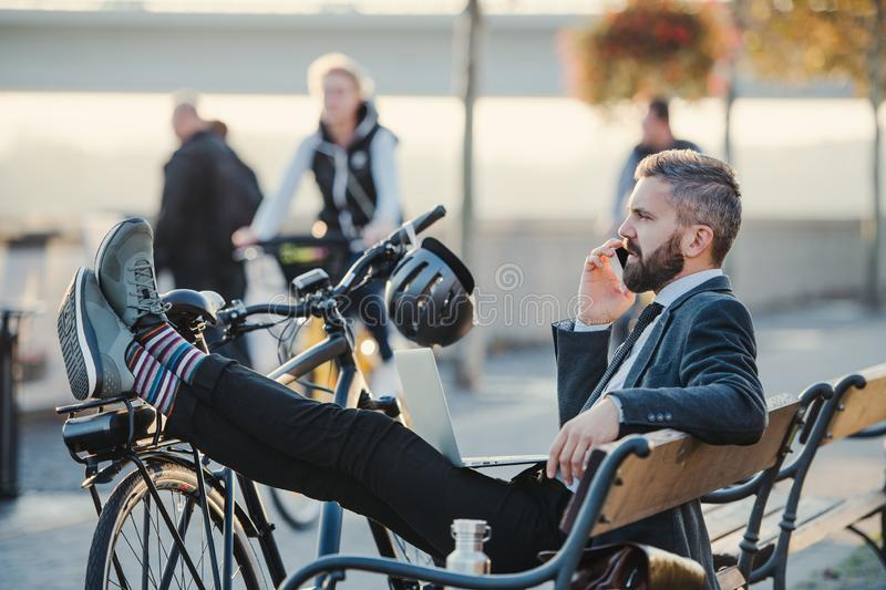 Businessman commuter with bicycle sitting on bench in city, making a phone call. A side view of businessman commuter with smartphone and bicycle sitting on stock image