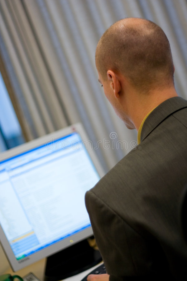 Businessman at Computer. A business man makes use of a desktop computer