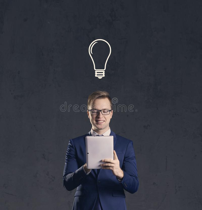 Businessman with computer tablet has idea. Dark and dramatic background. Business, solution, concept. stock image