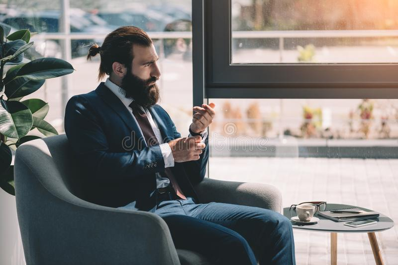 Businessman. Concentrated young bearded businessman looking through window royalty free stock image