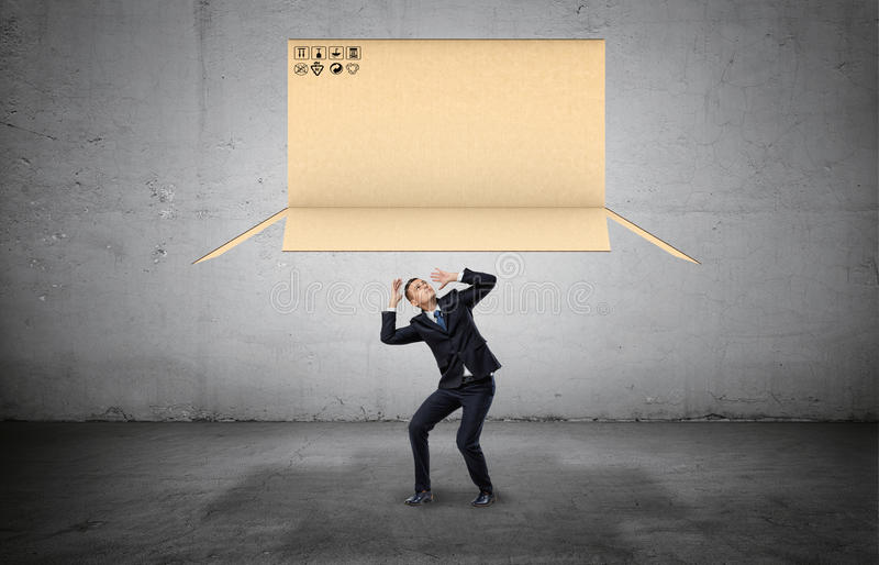 Businessman on concrete background cowering below a large open carton box falling on him. Business and success. Obstacles and limitations. Risk and danger royalty free stock image