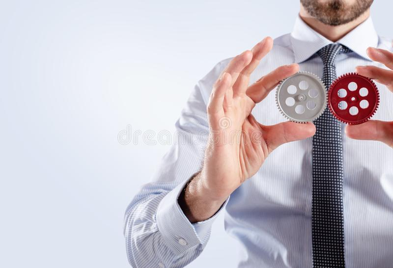 Businessman connects gears. Teamwork and partnership concept royalty free stock photo