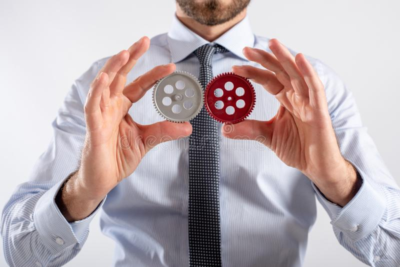 Businessman connects gears. Teamwork and partnership concept royalty free stock images