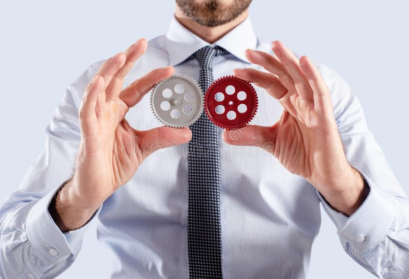 Businessman connects gears. Teamwork and partnership concept royalty free stock photography