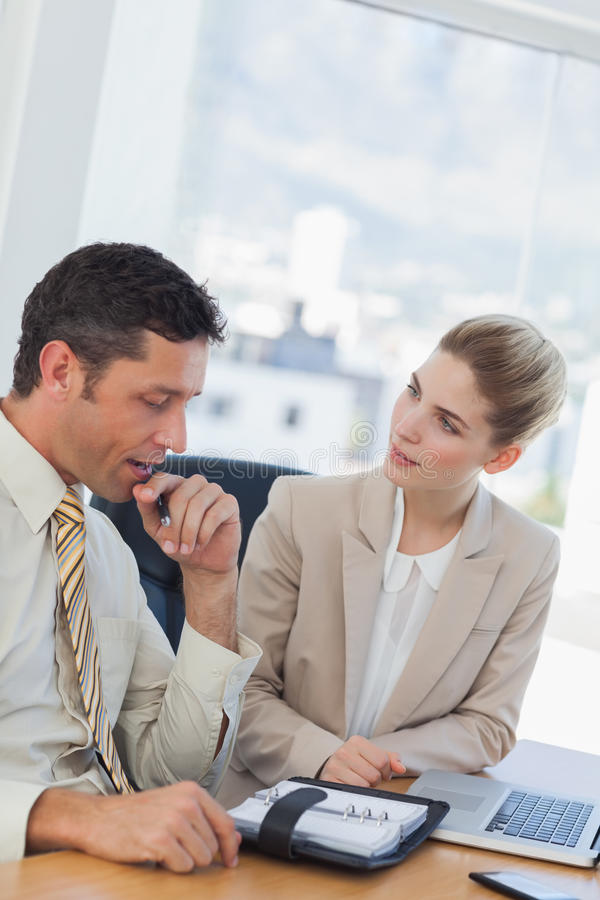 Businessman consulting his agenda while talking to his colleague stock photography
