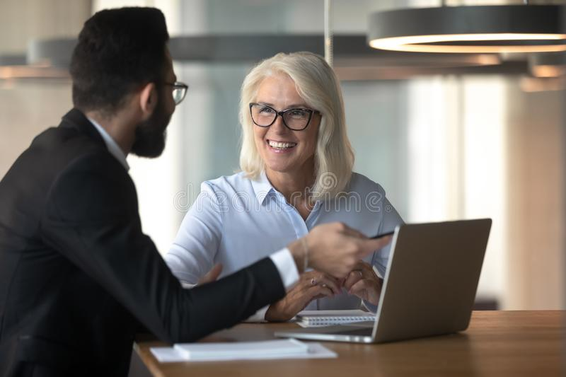 Businessman consulting mature businesswoman client, using laptop stock photo