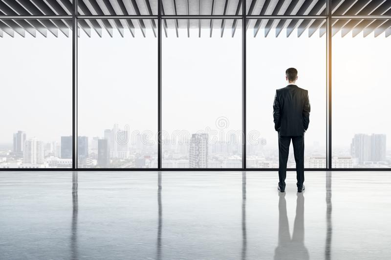 Businessman in contemporary office. Back view of businessman standing in contemporary office interior with panoramic city view, reflections on concrete floor and stock photography