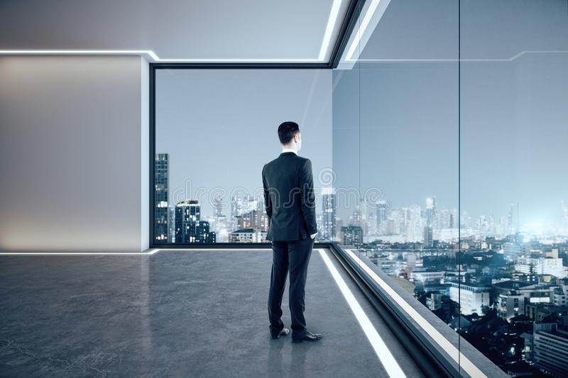 Businessman in contemporary office. Businessman looking out of window in contemporary empty spacious office interior with illuminated panoramic city view stock photography