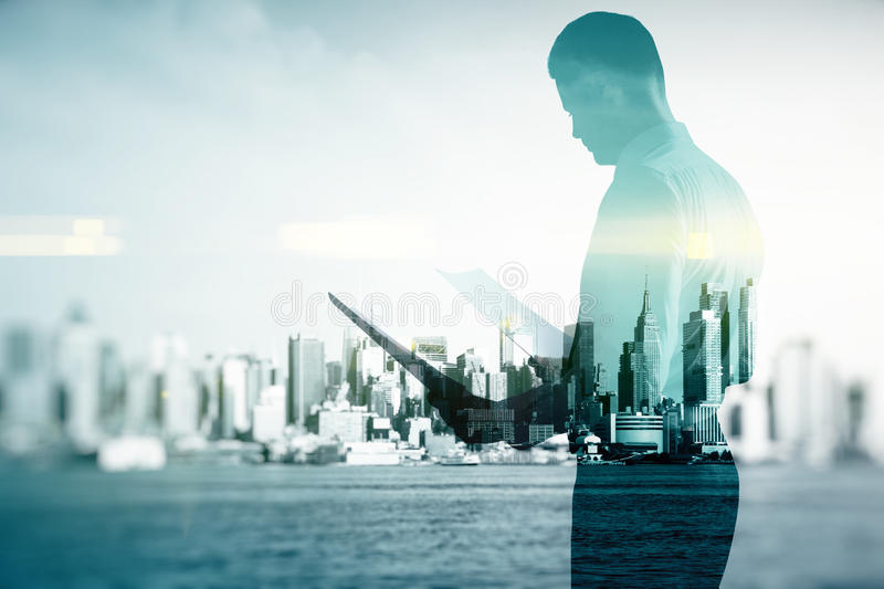 Businessman with contract. Side view of young businessman examining contract/document on abstract city background. Double exposure stock image