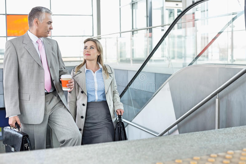 Businessman conversing with female colleague while walking up stairs in train station royalty free stock photo